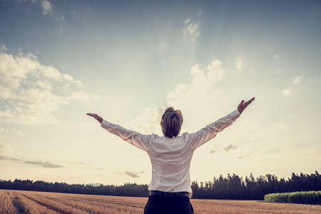 Photo for Retro image of victorious young businessman celebrating his success and achievement by standing under majestic sky raising his arms in gratitude and contentment. - Royalty Free Image