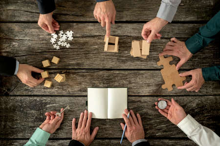 Photo for Eight businessmen planning a strategy in business advancement each holding  different but equally important metaphorical element - compass,  puzzle pieces, pegs, cubes, key and one making notes. - Royalty Free Image