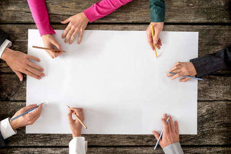Photo for Teamwork and cooperation concept - top view of six people - men and women - drawing or writing on a large white blank sheet of paper. - Royalty Free Image