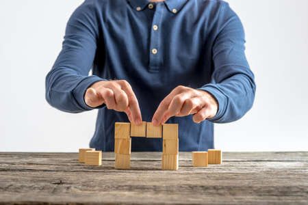 Photo pour Front view of a man making a bridge with wooden cubes. Conceptual of business, education and construction. - image libre de droit