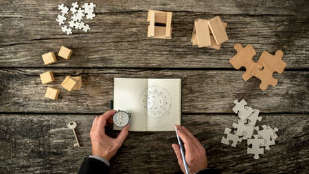 Photo pour Businessman making plan and business strategy decisions as he sketches a compass he is holding into his notebook. Various cubes, pegs, puzzles and a key lying on his wooden office desk, top view. - image libre de droit