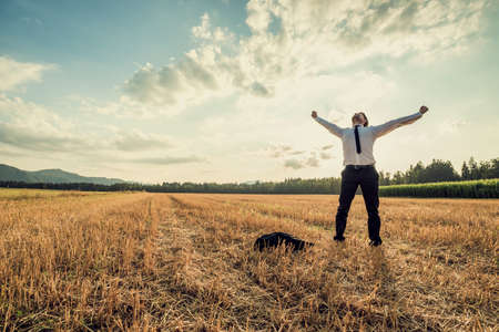 Foto de Successful businessman standing victoriously in the middle of field raising his arms in celebration and relief as he stands under majestic evening sky with his jacket lying on the floor next to him. - Imagen libre de derechos
