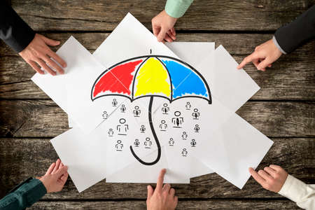 Foto de Safety and life insurance concept - six hands assembling a colourful umbrella sheltering many people icons drawn on white papers. - Imagen libre de derechos
