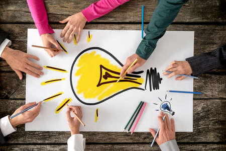 Foto de Top view of six people, men and women, drawing bright yellow light bulb on a large sheet of paper or placard. Conceptual of teamwork, research, education and innovation. - Imagen libre de derechos