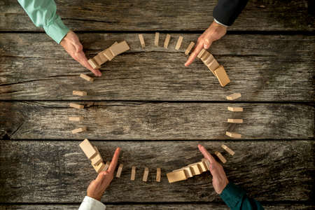 Foto de Hands of four businessmen joining forces  as a team to stop wooden pegs from falling. Business concept of teamwork, crisis solution and problem management. - Imagen libre de derechos