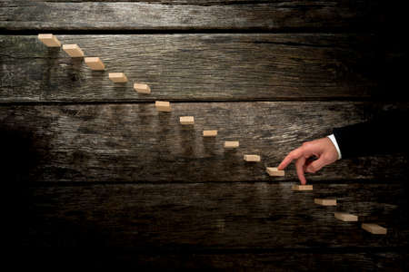 Photo pour Businessman walking his fingers up wooden steps towards light resembling a staircase in rustic wooden boards in a conceptual image of personal growth, development and achievement. - image libre de droit