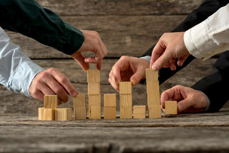 Foto de Hands of five businessman holding wooden blocks placing them into a structure. Conceptual of teamwork, strategy and business start up. - Imagen libre de derechos