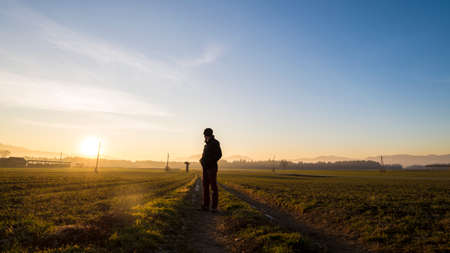 Photo pour Young man standing on country road in a beautiful landscape looking back towards a setting evening sun. - image libre de droit