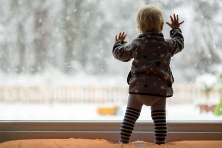 Foto de View form behind of toddler child standing in front of a big window leaning against it looking outside at a snowy nature. - Imagen libre de derechos