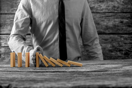 Foto de Greyscale image of businessman stopping falling dominos with his hand with selective colour of the dominos. - Imagen libre de derechos