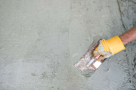 Photo pour Workman or builder doing plastering of a concrete surface, top view of his hand and tool in a DIY, renovation and construction concept, with copy space. - image libre de droit