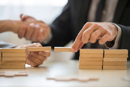 Photo pour Teamwork or building bridges concept with a businessman and woman holding wooden building blocks to form a bridge over a gap while clasping hands in the background. - image libre de droit