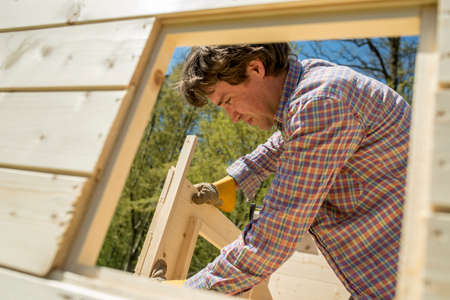 Photo for Carpenter or DIY homeowner building a wooden hut outdoors in the garden fitting the window and door frames viewed through a window opening. - Royalty Free Image