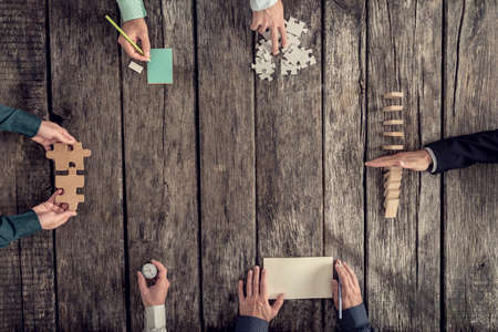 Foto de Business strategy and brainstorming concept with a team of six businessmen holding puzzle pieces, writing down ideas on paper and stopping domino effect, top view. - Imagen libre de derechos