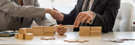 Photo pour Businessman and businesswoman holding wooden building blocks to form a bridge over a gap while shaking hands. - image libre de droit