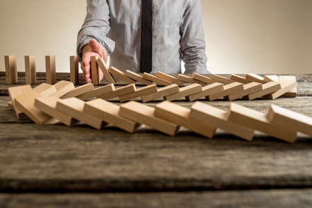 Foto de Hand stopping domino effect of wooden blocks for concept about business and accountability. - Imagen libre de derechos