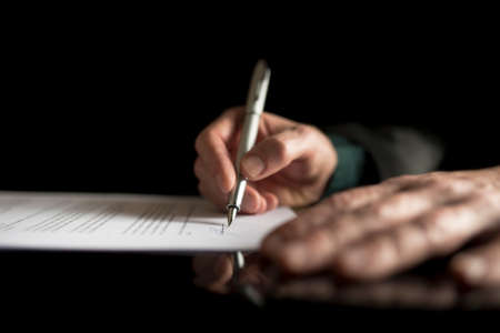 Photo pour Low angle view of a male hand signing contract or subscription form with a pen on black desk. - image libre de droit