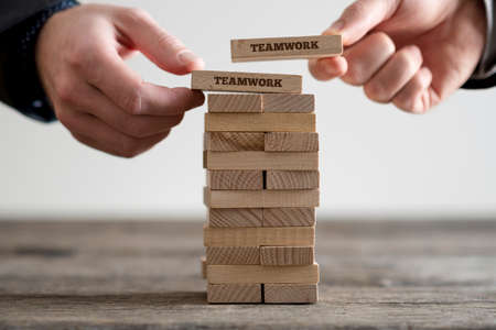 Foto de Two hands putting dominoes onto stack of wooden bricks with teamwork business signs on rustic table surface. - Imagen libre de derechos
