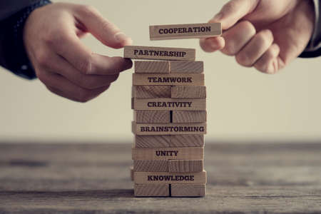 Foto de Close-up of hands putting dominoes onto stack of wooden bricks with motivational business signs on brown table surface, vintage effect toned image. - Imagen libre de derechos