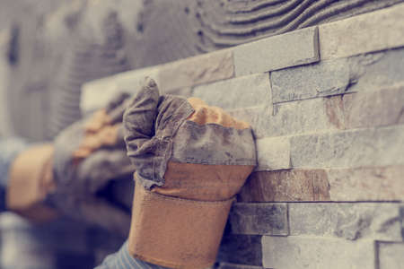 Photo for Retro effect faded and toned image of hands of tiler worker in gloves pressing brick tiles to stick it to the wall. - Royalty Free Image