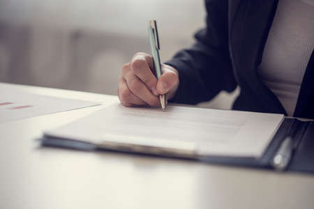 Photo pour Retro vintage style image of a businesswoman signing a contract or document on a map. - image libre de droit