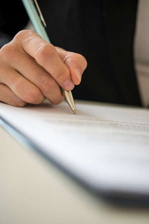 Photo pour Low angle view of a woman signing contract with a pen. - image libre de droit