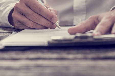 Foto de Retro effect faded and toned image of male hand signing business contract or document with fountain pen on old rustic wooden desk. - Imagen libre de derechos
