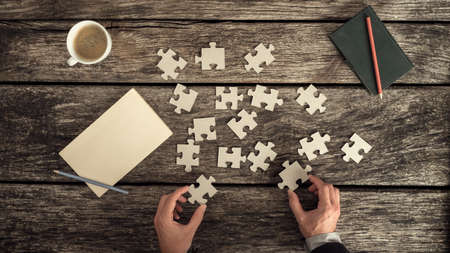 Foto de Retro style image of male hands in business suit trying to find a solution to a problem by arranging and matching puzzle pieces on a textured rustic wooden desk, top view. - Imagen libre de derechos