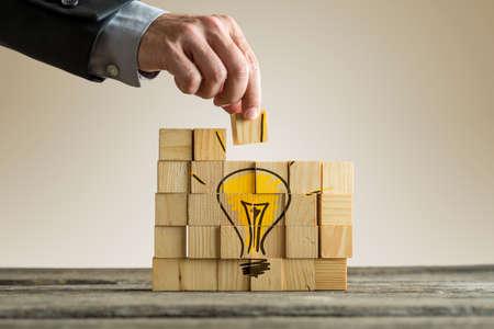 Foto de Brainstorming concept with businessman arranging wooden blocks forming a yellow light bulb on a rustic table. - Imagen libre de derechos