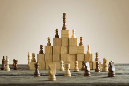 Foto de Business hierarchy; ranking and strategy concept with chess pieces standing on a pyramid of wooden building blocks with the king at the top with copy space. - Imagen libre de derechos