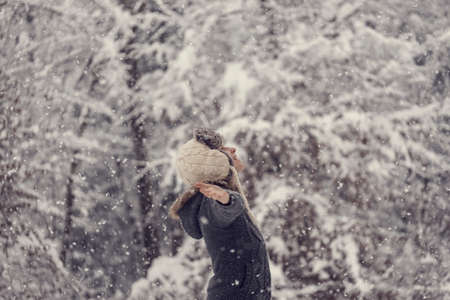 Foto de Retro effect faded and toned image of a woman celebrating winter standing outdoors in falling snow with her arms outspread. - Imagen libre de derechos