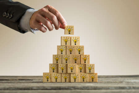 Foto de Businessman stacking a tower of wood blocks with yellow light bulbs in a form of a pyramid conceptual of innovation, development and vision. - Imagen libre de derechos