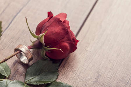 Foto de Top view of a single red rose with marriage or engagement ring around it on wooden table, retro effect faded look. - Imagen libre de derechos
