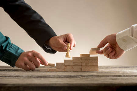 Foto de Business teamwork concept with a businessman moving a chess piece queen up a series of steps formed by blocks being put in place by his team. - Imagen libre de derechos