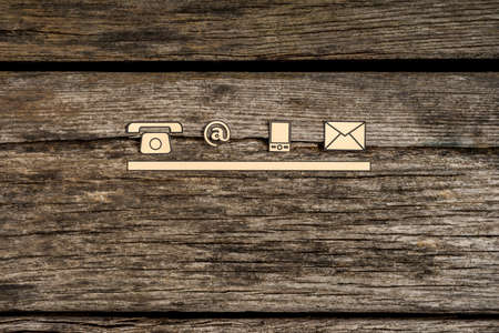 Foto de Contact and communication icons, telephone, at sign, mobile and mail, on textured rustic wooden boards. - Imagen libre de derechos