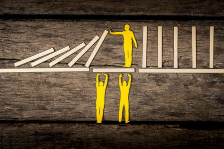 Foto de Small yellow paper person holding up falling blocks while standing on white platform held up by two other yellow figures. - Imagen libre de derechos