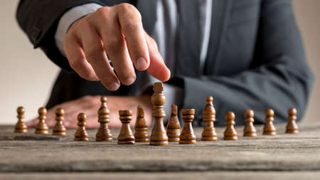 Photo pour Businessman wearing business suit reaching dark King chess piece at wooden table. Conceptual of business vision, progress and success. - image libre de droit