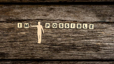 Photo pour Impossible versus Possible concept with a paper cut out man pushing away the litters IM on a rustic weathered wood background. - image libre de droit