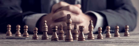 Photo pour Retro style image of a businessman with clasped hands planning strategy with chess figures on an old wooden table. - image libre de droit