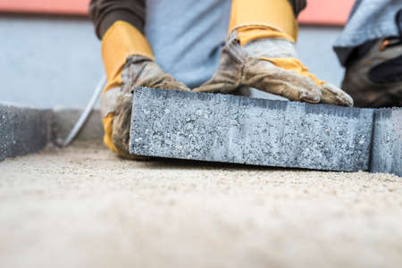 Photo for Building contractor laying a paving slab or brick placing it on the sand foundation with gloved hands in a low angle view. - Royalty Free Image