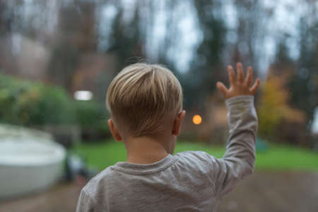 Little boy standing staring out of a window in evening light into the garden with his hand spread out on the glass viewed from behind.