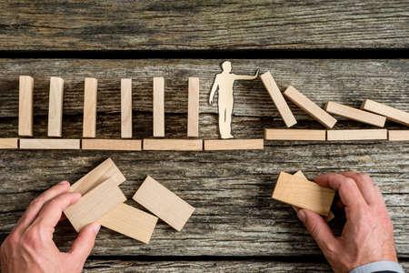 Foto de Conceptual close-up of the hands of a man building a stable bridge or a structure for a paper man stopping the collapse of wooden blocks. - Imagen libre de derechos