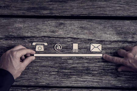 Foto de Communications concept with phone, website, and mail icons in a row supported by the hands of a businessman over a rustic rough wood background. - Imagen libre de derechos