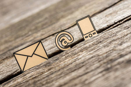 Foto de Contact and communication icons mobile phone, at sign and mail on textured rustic wooden table. - Imagen libre de derechos