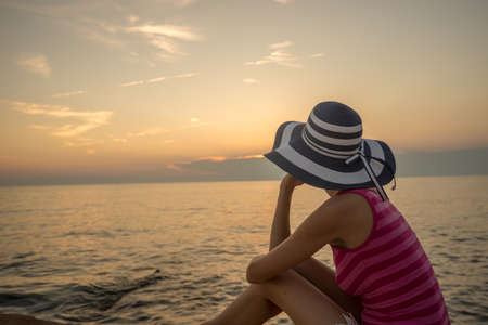 Photo for View from behind of a woman wearing striped pink shirt and blue straw hat looking at the sunset over sea. - Royalty Free Image