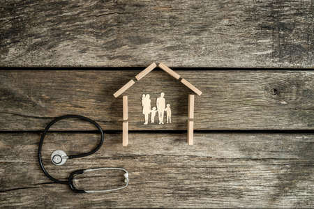 Foto de Cut outs of a young family with kids in a house with a stethoscope lying on a rustic wood background alongside in a conceptual image. - Imagen libre de derechos