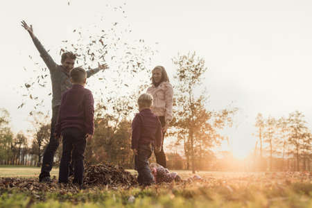 Foto de Young family playing with autumn leaves standing in a circle in nature tossing them into the air and laughing, retro effect faded look. - Imagen libre de derechos