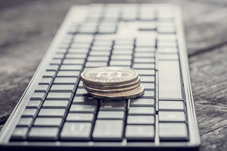 Foto de Retro effect faded and toned image of a keyboard with pile of golden coins with Bitcoin sign. - Imagen libre de derechos