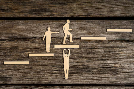 Photo for Cut outs of paper men with one supporting steps, one giving a helping push from behind and the third climbing the steps to success in a conceptual image. - Royalty Free Image