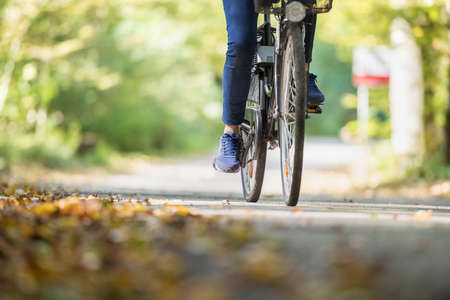 Photo for Woman riding a bicycle outdoors on a path in the park in Autumn. - Royalty Free Image